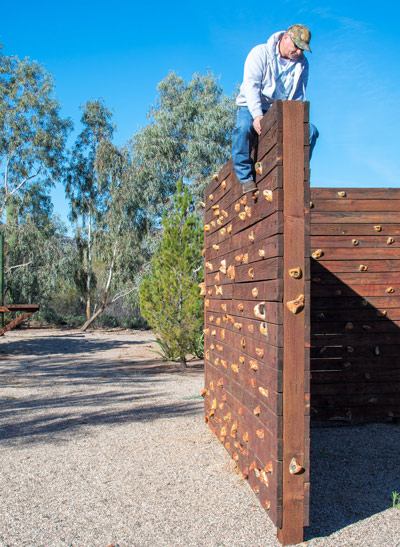 man climbing wall on low ropes course - Cottonwood Tucson - recreation therapy