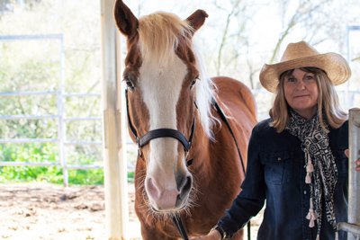smiling woman with horse - Cottonwood Tucson - trauma therapy