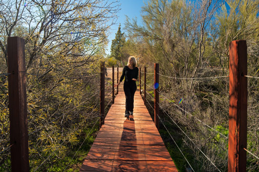 woman walking on wooden bridge