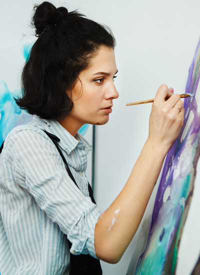 pretty young brunette woman painting - art therapy - post-traumatic stress disorder